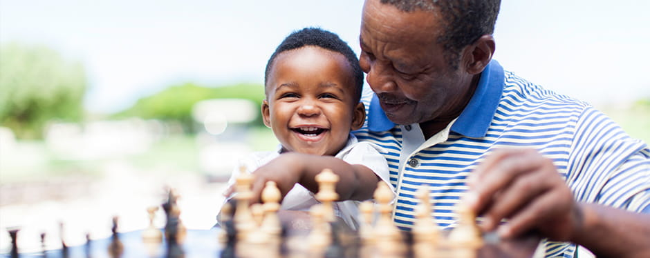 Image of man playing chess with grandson