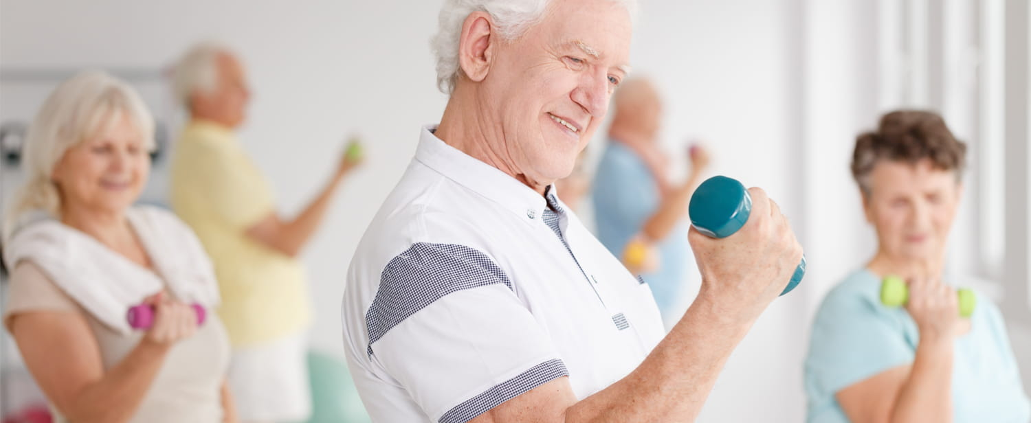 Man curling dumbbell in fitness class